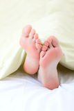Feet under blanket Stock Photo