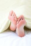 Feet under blanket Stock Photo