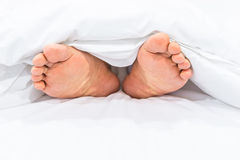 Feet under the blanket Royalty Free Stock Photos