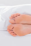 Feet under a duvet Stock Photos