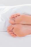 Feet under a duvet. In a bed Stock Photos