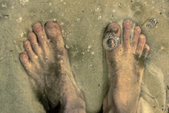 Feet under the water standing on sandy bottom and bubbles on wat Stock Photography