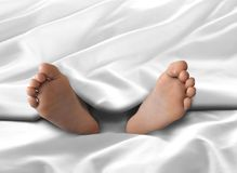Feet under White Blanket and Bed Sheet Stock Photography