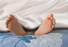 Feet under white blanket Stock Photo