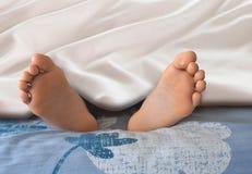 Feet under white blanket. Image of feet under white blanket Stock Photo
