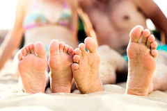 Feet of unrecognizable couple sitting on the sandy beach Royalty Free Stock Image