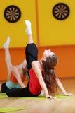 Feet up. Young women making aerobics exercises raising feet up stock photos