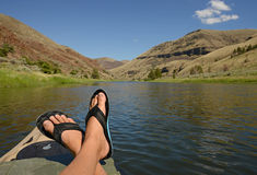 Feet up while relaxing during leisure time on a kayak. Feet up while relaxing during leisure time on a river with mountains Stock Images