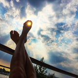 Feet up in the sun. Girls feet up to the sun over a rail of a balcony. The sun is shining through the tooth. Image taken in the from below up to the sky royalty free stock photos