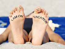 Feet on vacation. Woman showing bare feet on beach blanket with smiley faces on toes and text I am on vacation in sunshine Stock Photos