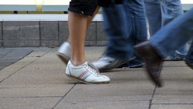 Feet walking. A foot wearing a casual white shoe is frozen against the motion of the feet of other passers by Royalty Free Stock Images
