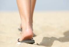 Feet walking in flip flops on beach. Close up low angle feet walking in flip flops on beach Stock Photography