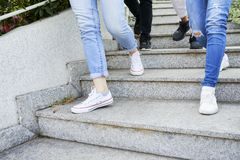 Feet of walking people. Feet of young people walking down the stairs in the street stock photo