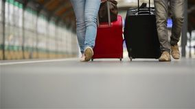 Feet walking on the platform passengers with a suitcase, young couple walking along the platform to the train with stock footage