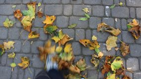 Feet walking on the road with yellow autumnal leaves stock footage