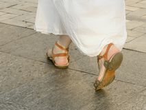 Feet walking on the sidewalk girl in a white dress and sandals.  Stock Images