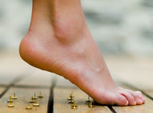 Feet almost walking on tacks, wooden floor Stock Photos