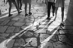 Feet walking on travertine floor in the Colosseum in Rome. Several pairs of feet walking on the travertine floor of the Colosseum in Rome, Italy casting long stock image