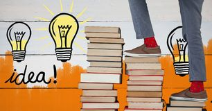 Feet walking up book stairs with colorful light bulb graphics and orange painted wall Stock Images