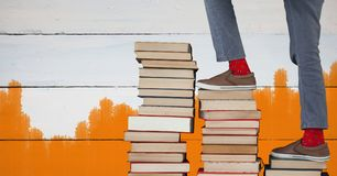 Feet walking up book steps and orange painted background Stock Photography