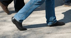Feet while walking in worn shoes. On asphalt road stock photos