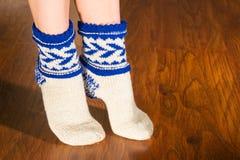 Feet warm beautiful socks on a wooden floor Royalty Free Stock Photos