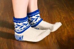 Feet warm beautiful socks on a wooden floor Stock Photos