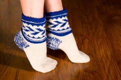 Feet warm socks. On dark wooden floor Stock Photos