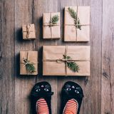 Feet with warm winter socks and cat slippers standing in front of Christmas gifts. top view. Feet with warm winter socks standing in front of Christmas gifts Royalty Free Stock Photography