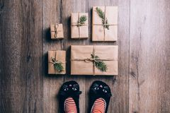 Feet with warm winter socks and cat slippers standing in front of Christmas gifts. top view. Feet with warm winter socks standing in front of Christmas gifts Stock Images