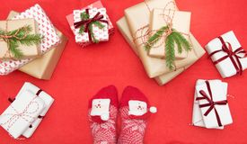 Feet with warm winter socks standing in front of Christmas gifts on red blanket. View from above. Xmas. royalty free stock images