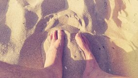 Feet in warm sand stock images