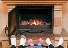 Feet warming at a fireplace stock photos