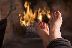 Feet warming at a fireplace Stock Images