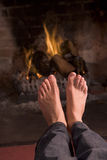 Feet warming at a fireplace Royalty Free Stock Photography