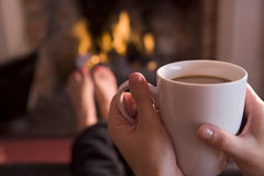 Feet warming at a fireplace with coffee. Feet warming at a fireplace with hands holding coffee Royalty Free Stock Images