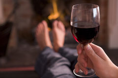 Feet warming at fireplace with hand holding wine Royalty Free Stock Photography