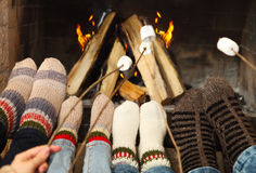 Feet warming at a fireplace with marshmallows on sticks Stock Images