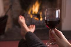 Feet warming at fireplace with wine