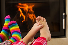 Feet warming by fireplace Stock Image