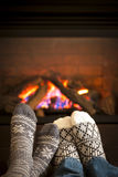 Feet warming by fireplace. Feet in wool socks warming by cozy fire Royalty Free Stock Photography