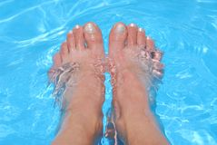 Feet in water. Woman's feet cooling in clear blue water Stock Photography