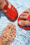 Feet on the water. Close-up of feet on the swimming pool water Royalty Free Stock Photography