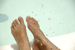 Feet and water. Feet by the pool side is being refreshed by cool water drops Stock Photos