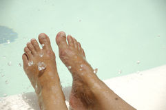 Feet and water. Feet by the pool side is being refreshed by cool water drops. The water drops are in motion blur Royalty Free Stock Photography