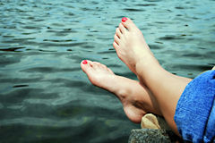 Feet by water. Feet dangling over the water stock photo