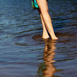 Feet in the water. Beautiful girl's legs in the morning on the seafront. The girl walks through the shallow water Stock Photography