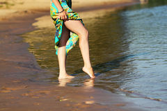 Feet in the water. Beautiful girl's legs in the morning on the seafront. The girl walks through the shallow water Royalty Free Stock Image