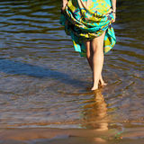 Feet in the water. Beautiful girl's legs in the morning on the seafront. The girl walks through the shallow water Stock Image