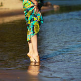 Feet in the water. Beautiful girl's legs in the morning on the seafront. The girl walks through the shallow water Royalty Free Stock Photos